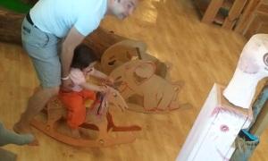 עלמה מתנדנדת על סוס מעץ