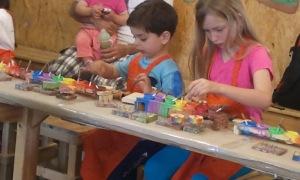 יהונתן ואורן צובעים את צעצועי העץ שבחרו